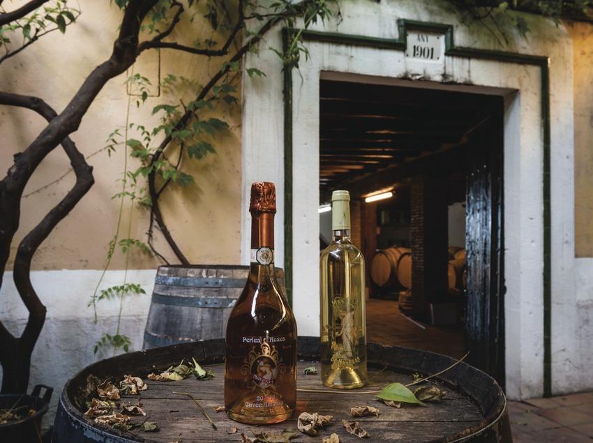 Caves Naveran, botellas de cava y vino sobre barrica en el patio y delante la puerta de la bodega con barricas.