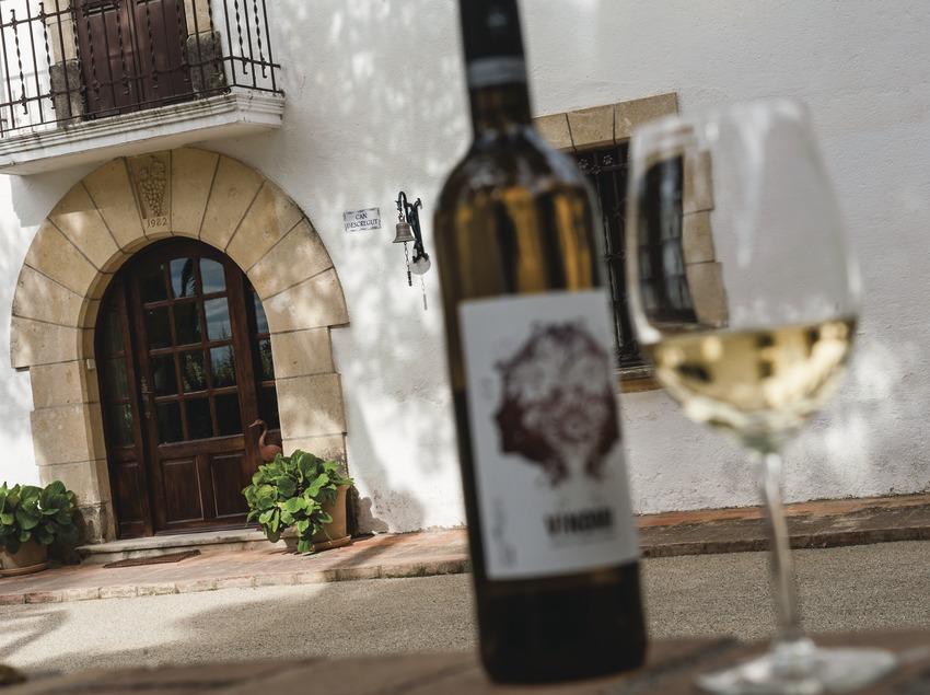 Can Descregut, ampolla i copa de vi amb la façana de la masia de fons.