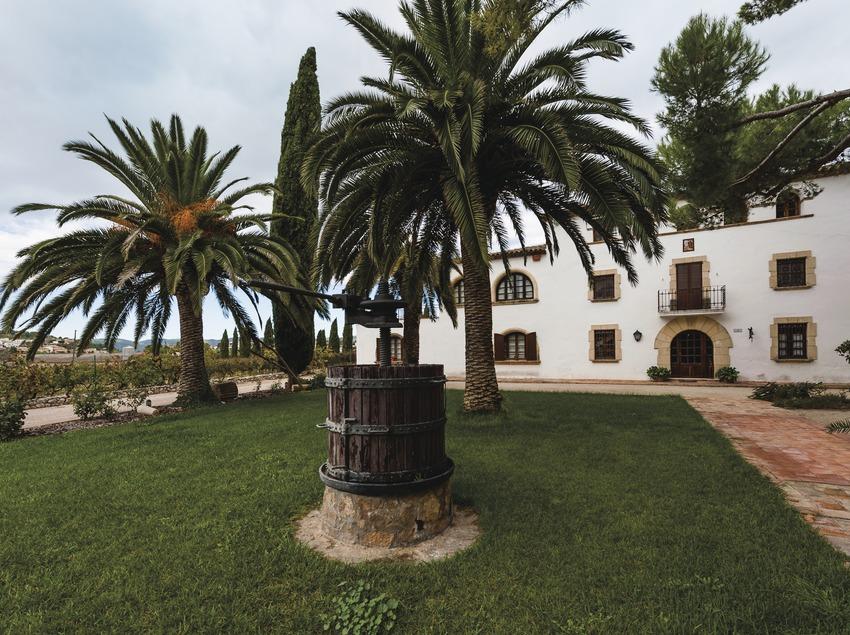Can Descregut, jardí amb premsa antiga i la masia de fons. (Marc Castellet)