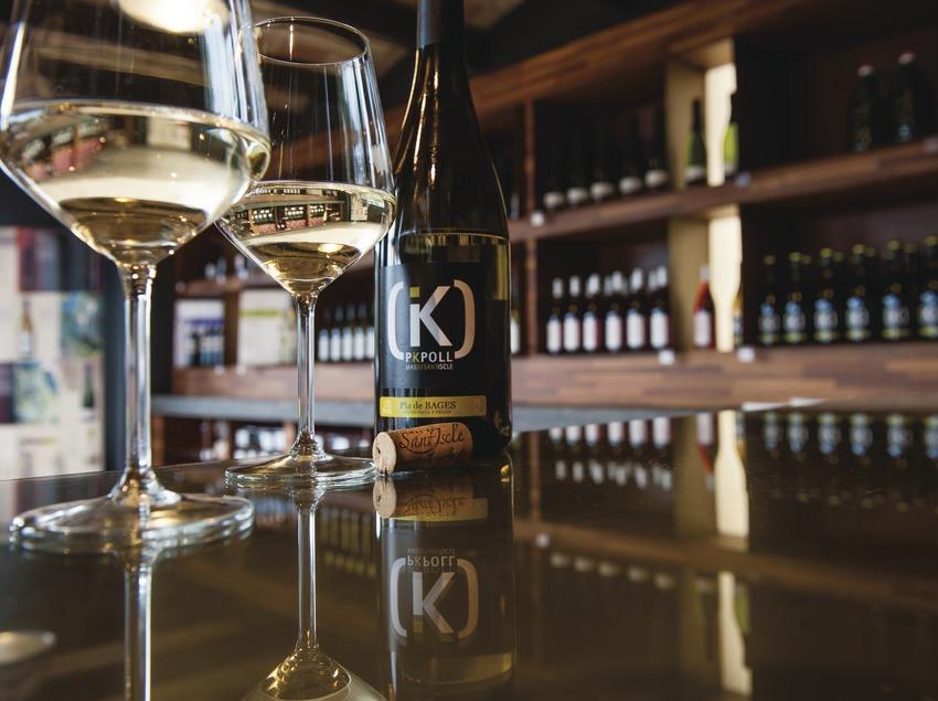 Mas de Sant Iscle, ampolla i copes de vi blanc dins la botiga-sala de degustació.