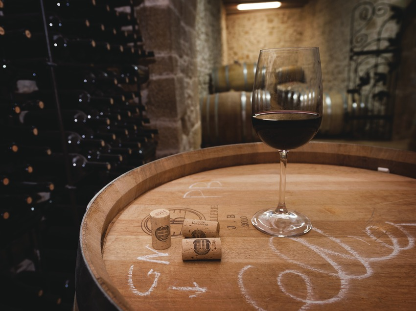 Celler la Bollidora, copa de vino y tapones con logotipo en la bodega, con barricas y botellas de fondo.