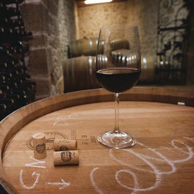 Celler la Bollidora, copa de vi i taps amb logotip al celler, amb barriques i ampolles de fons.