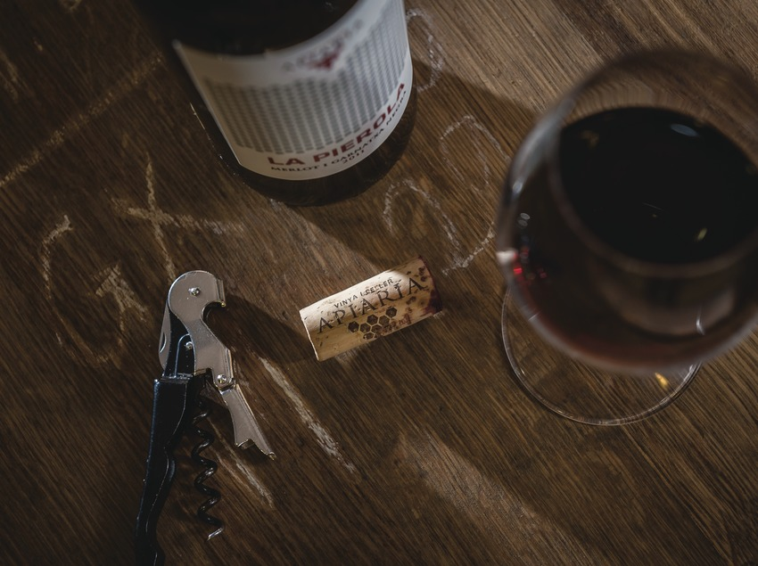 Apiaria, bodegó sobre barrica amb ampolla tap i copa de vi.