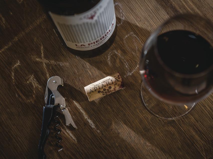 Apiaria, bodegón sobre barrica con botella, tapón y copa de vino.