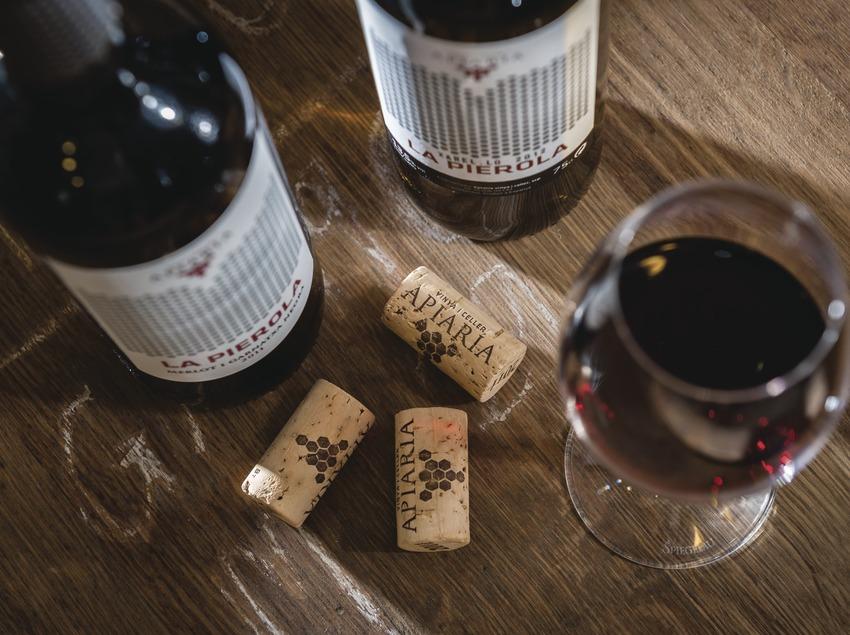 Apiaria, bodegó sobre barrica amb ampolles taps i copa de vi.