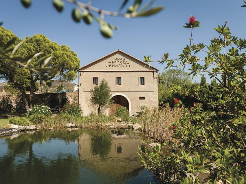 Gelamà, fachada de la cava con el estanque y los olivos delante. (Marc Castellet)