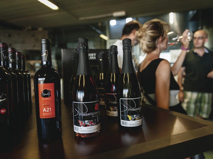Masetplana, ampolles en primer pla i visitants degustant vi de fons.