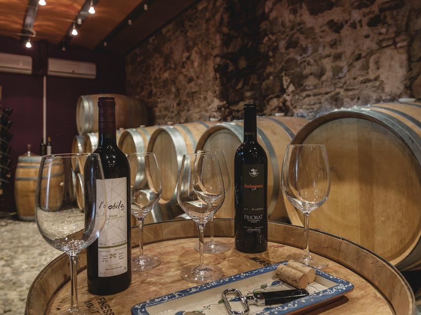 Costers del Ros, copas y botellas de vino en la sala de degustación y bodega.