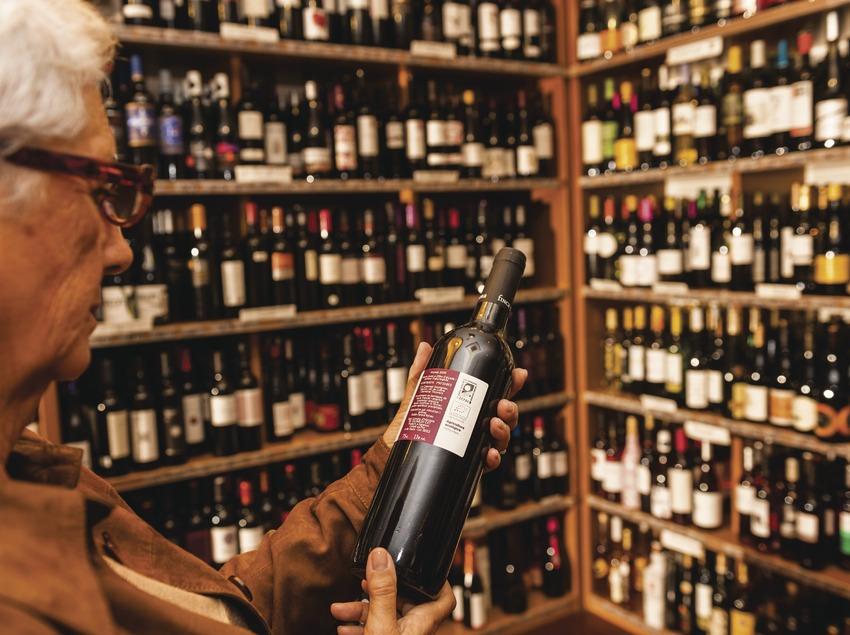 El Celler de la Boqueria. Senyora amb ampolla de vi i prestatges. Botiga amb ampolles de fons. (Marc Castellet)