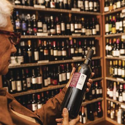 El Celler de la Boqueria. Señora con botella de vino y estantes. Tienda con botellas de fondo.