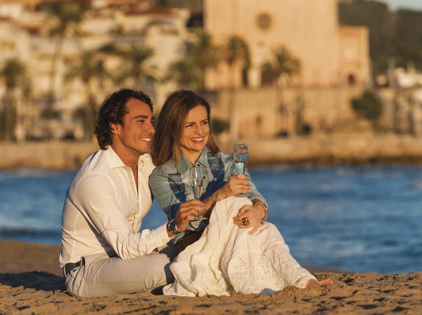 Cava y playa de Sitges. Pareja sentada en la playa de Sitges contemplando la puesta de sol con copas de cava   (Marc Castellet)