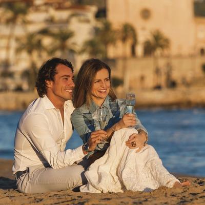 Cava y playa de Sitges. Pareja sentada en la playa de Sitges contemplando la puesta de sol con copas de cava.