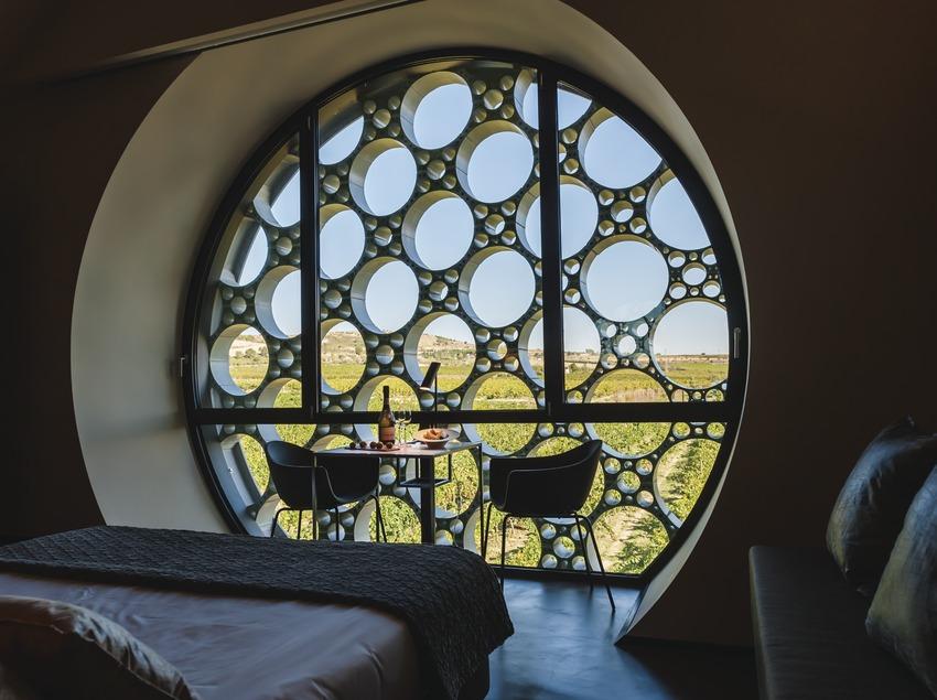 Hotel Mas Tinell. interior d'una habitació amb vistes de les vinyes i taula de benvinguda parada   (Marc Castellet)