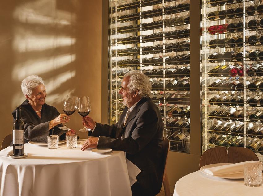 Hotel Mercer. Parella sènior brindant amb vi al restaurant amb vitrina d'ampolles de vi de fons.