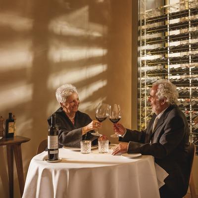 Hotel Mercer. parella sènior brindant amb vi al restaurant amb vitrina d'ampolles de vi de fons   (Marc Castellet)