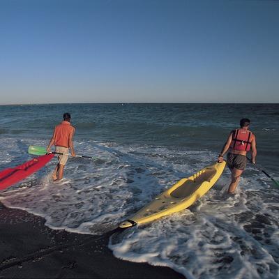 Canoas a punto de entrar en el agua en la playa del arenal de Hospitalet de l'Infant.