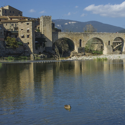 Pont i cases de Besalú amb el riu Fluvià en primer pla   Aquestes imatges han estat adquirides a través del projecte Eurocat dins el programa comunitari POCTEFA i, en aquest sentit la seva exhibició pública ha de portar els logos del seu finançament comunitari.  (@ Departament de Presidència de la G
