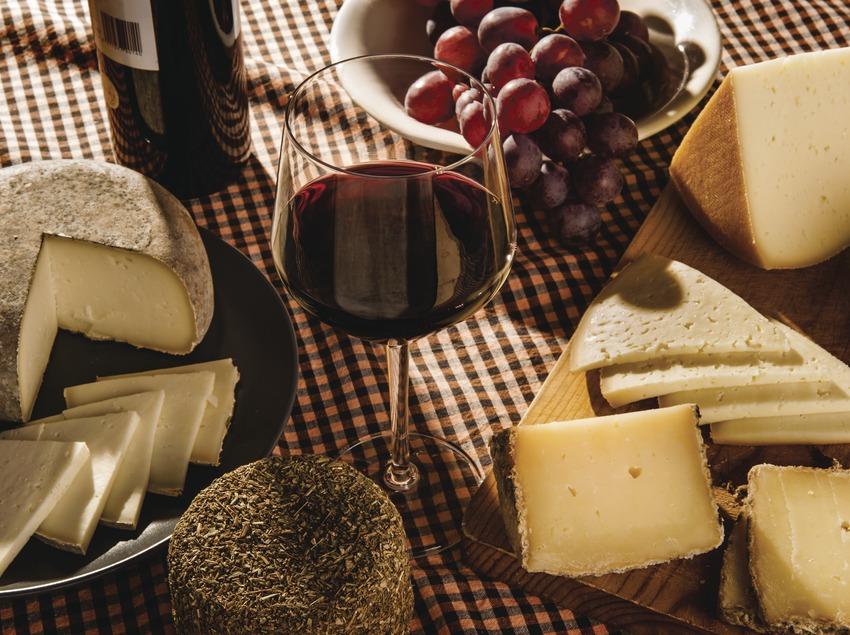 Vino y queso. Copa de vino acompañada de un racimo de uvas y quesos catalanes. Bodegón.