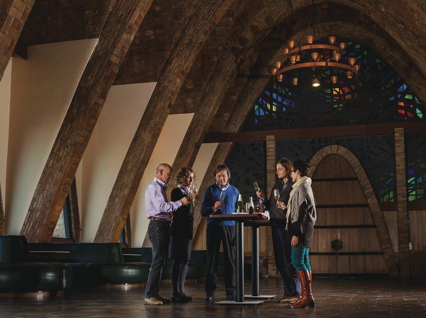 Caves Codorniu. Grup de gent fent un tast de cava dins d'una nau modernista.