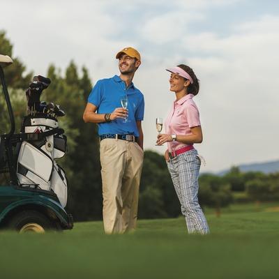 Club de Golf Peralada. Parella de jugadors de golf amb copa de cava.