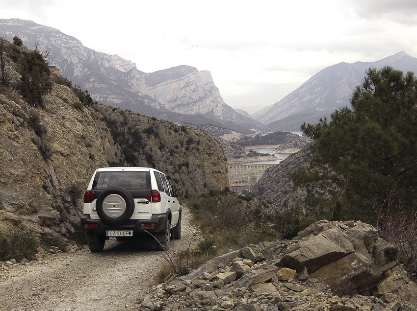4x4 trip on the track leading to the Castell-llebre chapel, in front of the Oliana dam and reservoir with the Serra d'Aubenç and the Serra de Turp mountains in the background