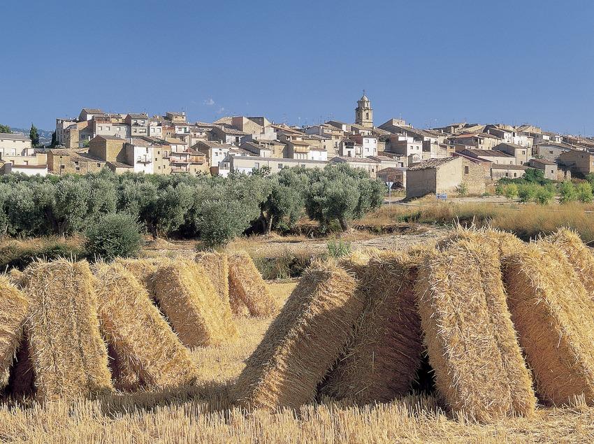 Fardos de paja y el pueblo de Arnes.  (Oriol Alamany)