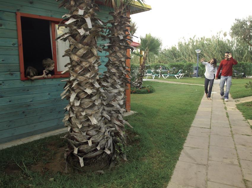 Parents saluant leurs enfants qui se trouvent à l'intérieur d'un bungalow du camping Sangulí Resort