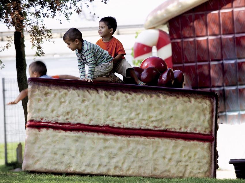 Enfants sur une énorme tranche de gâteau au parc pour enfants Francesc Macià