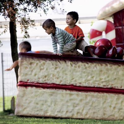Nens sobre un tros gegant de pastís al parc infantil Francesc Macià