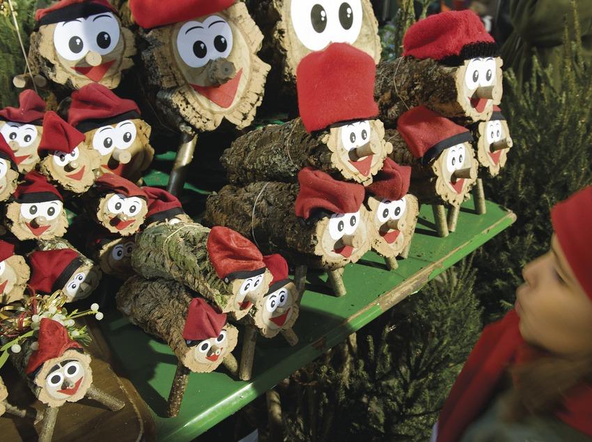 Un niño mira un grupo de caganers de diferentes tamaños con cara y barretina catalana. Feria de Navidad de Santa Llúcia (Gemma Miralda)