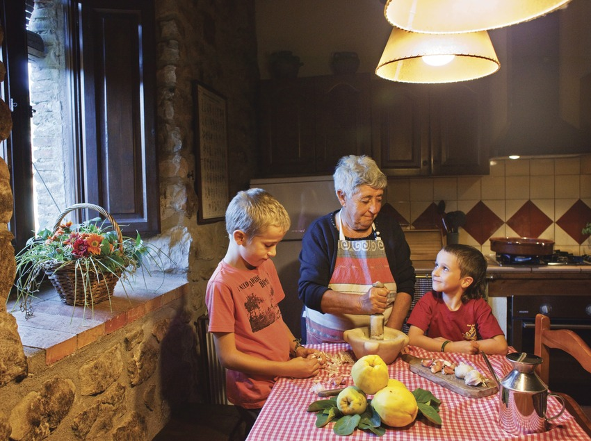 Una àvia amb els néts, a la cuina, preparant un all i oli de condony. Lladurs (Solsonès) (Oriol Clavera)