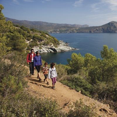 Senderisme en família a Cap de Creus. Camí de Ronda entre Roses i Cala Montjoi. Al fons, el Cap de Norfeu.