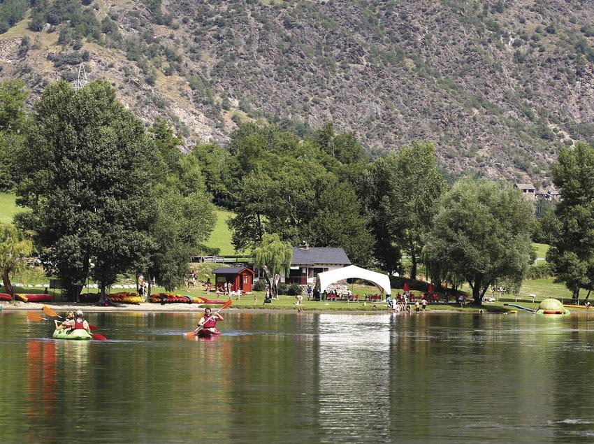 Gent remant en caiac per un llac.