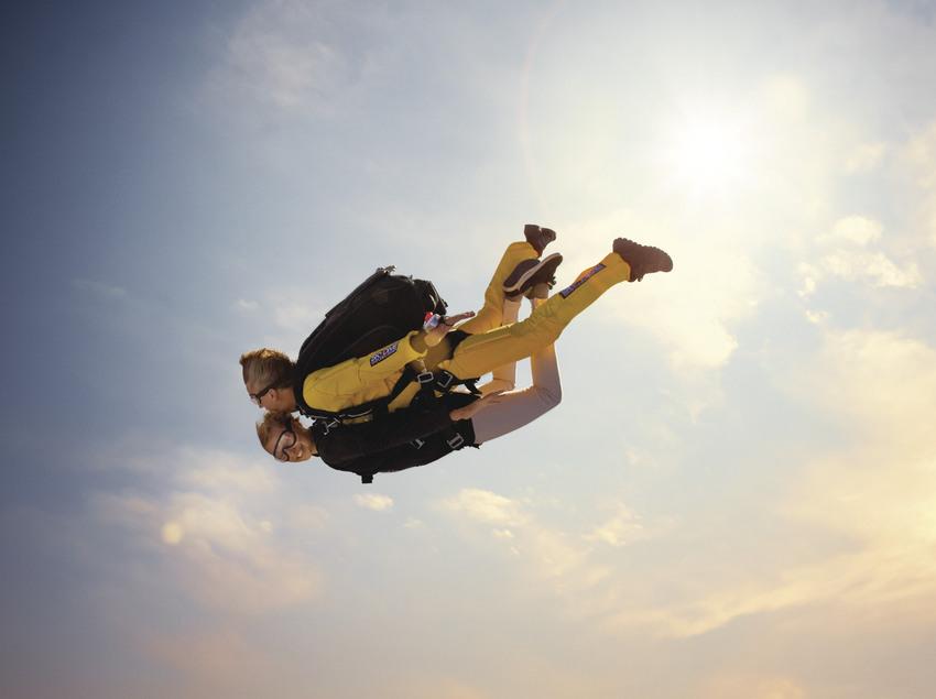 Instructor y alumno de paracaidismo descendiendo durante un salto tándem.