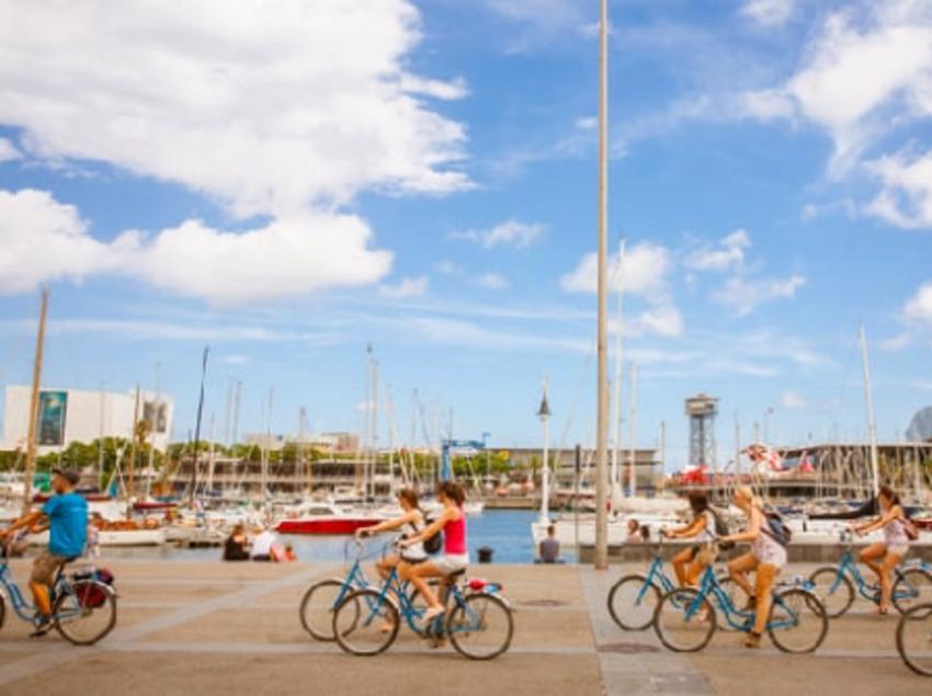 Grup de persones amb bicicleta passejant pel port de Barcelona.