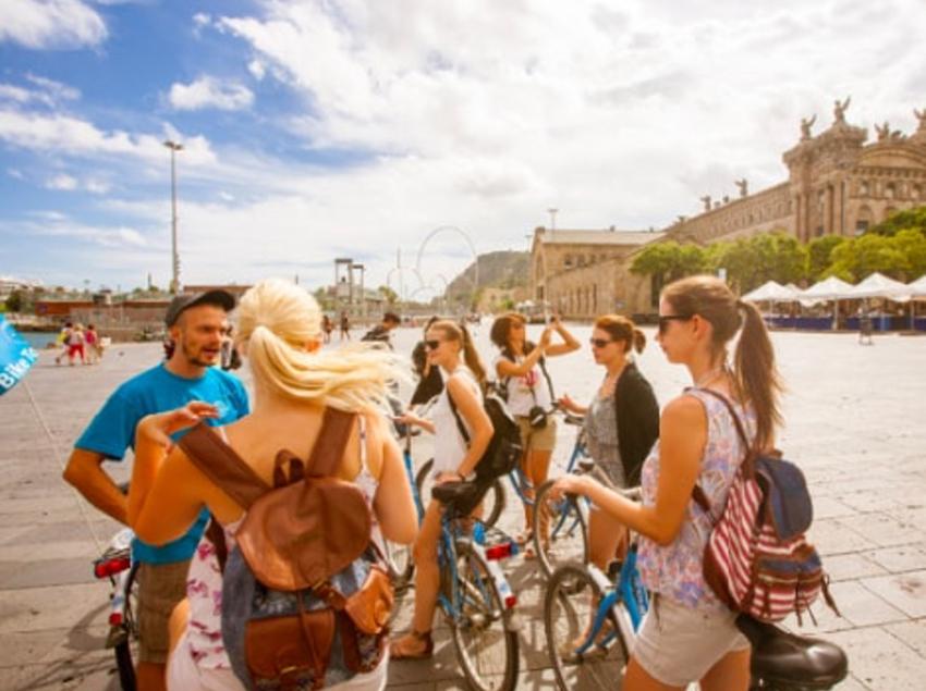 Grup de persones amb bicicleta passejant per Barcelona.