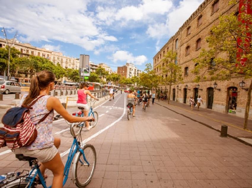 Grup de persones amb bicicleta passejant pel centre de Barcelona.