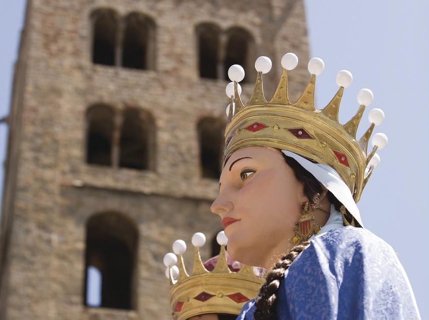Pareja de gigantes con el campanario del monasterio de fondo.