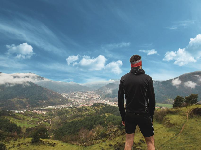 Corredor observando el paisaje de montaña.