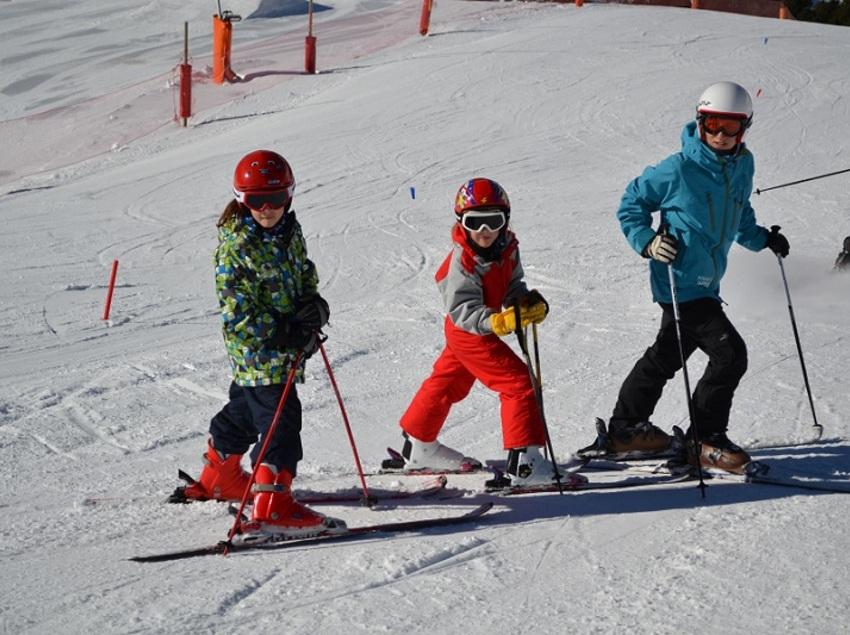 Niños esquiando con monitor