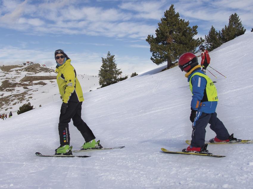 Niño con una monitora de esquí
