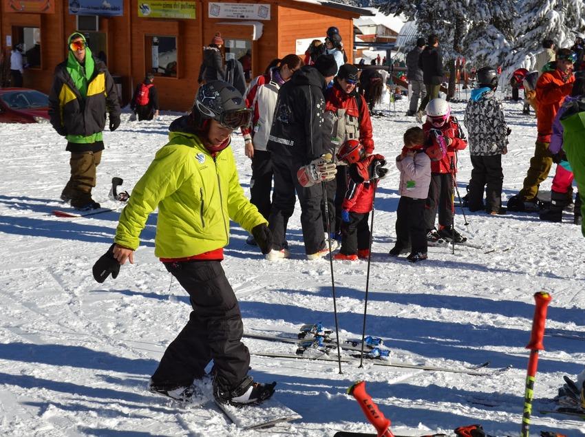 Gent equipant-se amb el material d'esquí i snowboard a l'esplanada davant la taquilla de l'escola.