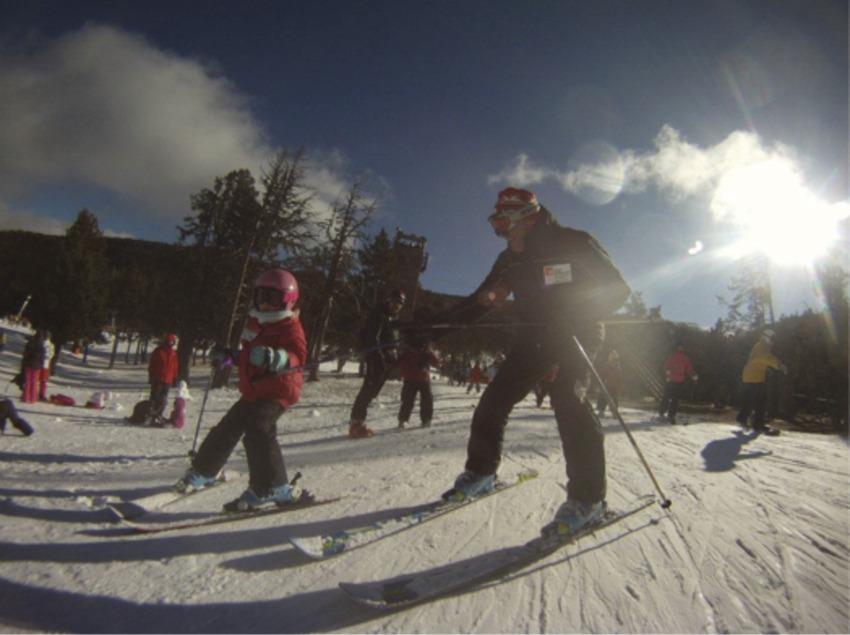 Professor ensenyant a esquiar un nen