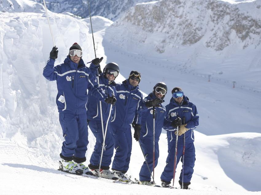 Grup d'esquiadors gaudint de la neu