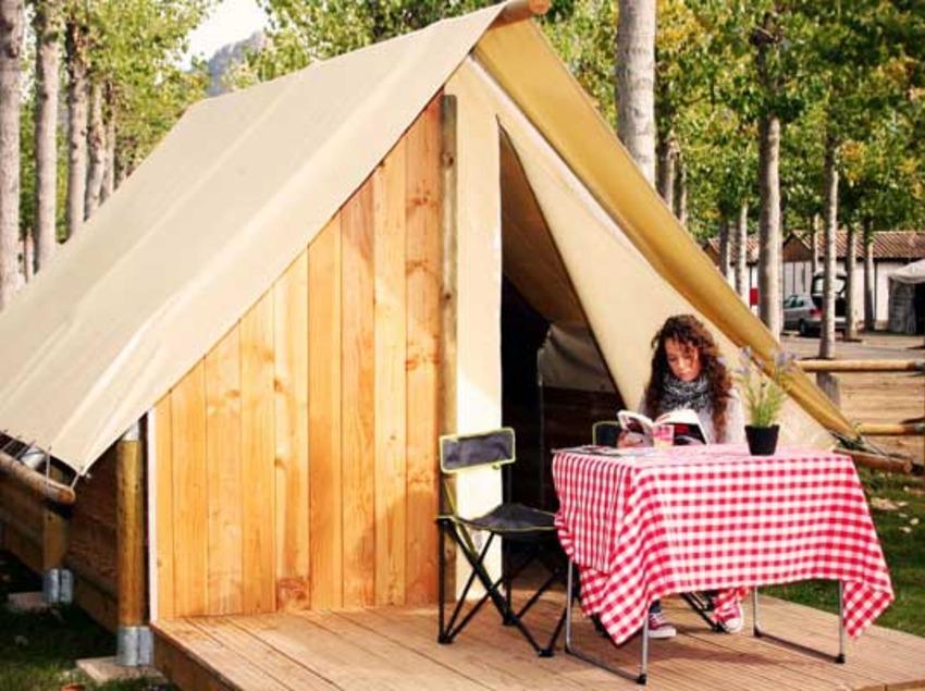 Gaudint de la lectura al costat de la tenda d'acampada