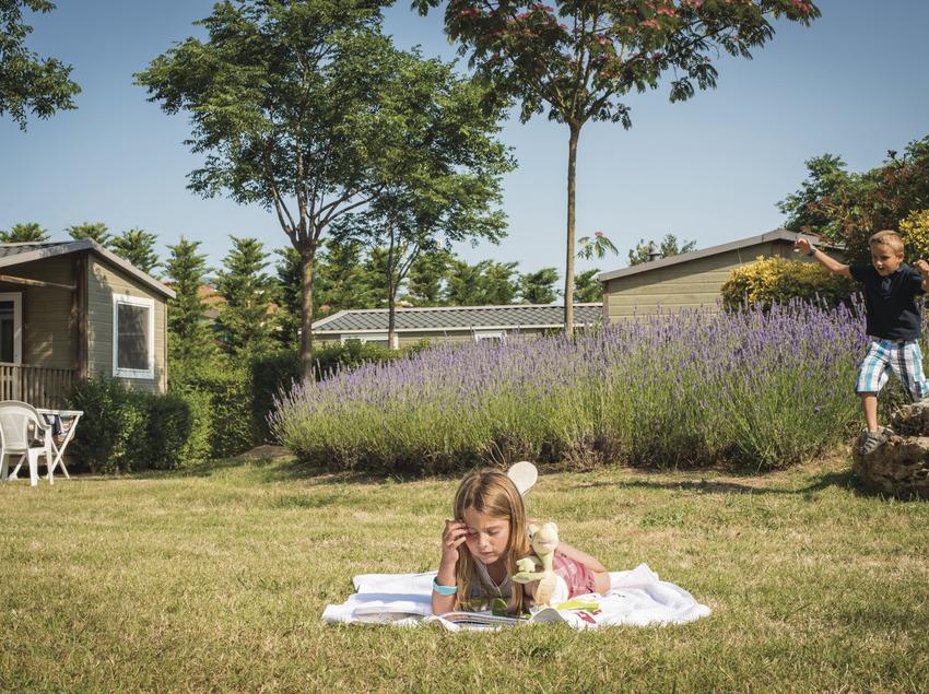 Nens jugant i llegint en un càmping