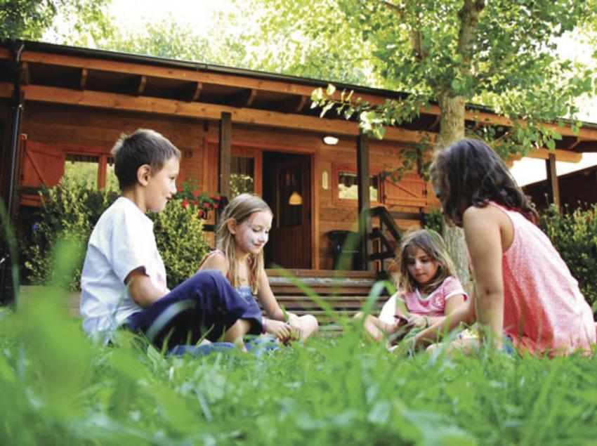 Grup de nens divertint-se al costat d'un bungalou
