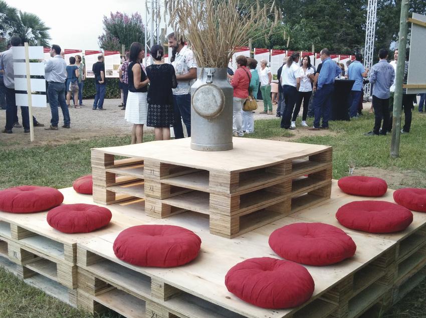 Seients fets de palets amb coixins vermells en un esdeveniment a l'aire lliure. (Atelier Esdeveniments)