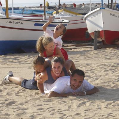 Familia haciéndose una fotografia al lado de unas barcas de pescadores en la playa de Calonge (Ajuntament de Calonge)