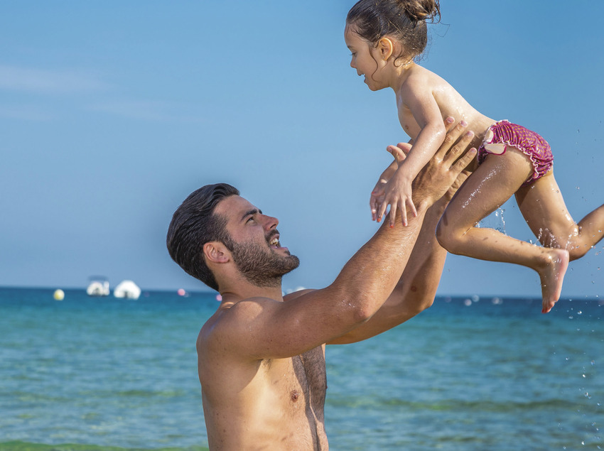 Pare i filla jugant a la platja de Sant Feliu de Guíxols (Ajuntament de Sant Feliu de Guíxols)